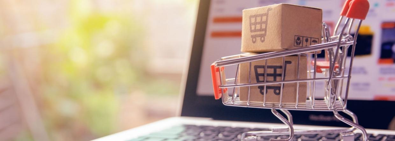 Een laptop die openstaat met een winkelmandje ervoor met een symbool voor online winkelen