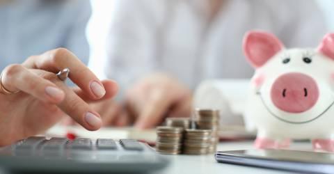 man en vrouw aan tafel met rekenmachine, geld en spaarvarken