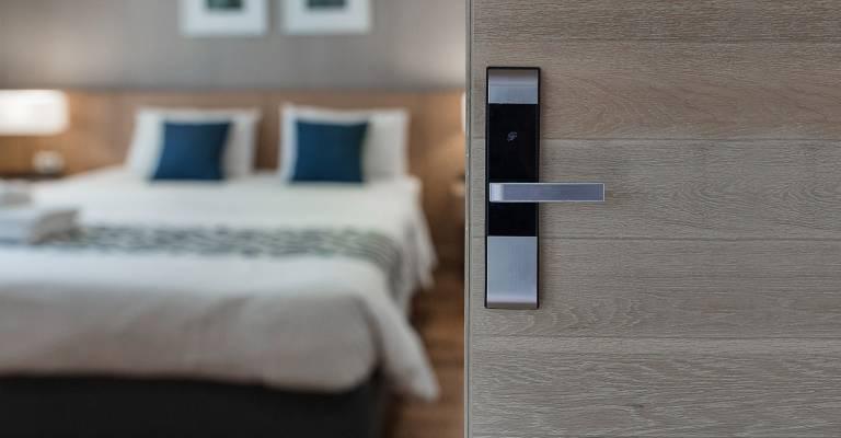 Open deur slaapkamer van vakantieverblijf met een bed op de achtergrond